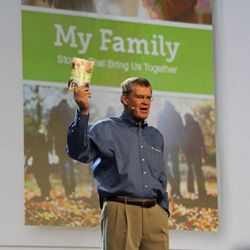 """Elder Dennis C. Brimhall, CEO of FamilySearch International and an Area Seventy of the Church, holds up a copy of the """"My Family"""" booklet during his address at the keynote session of RootsTech 2014 on Feb. 6."""