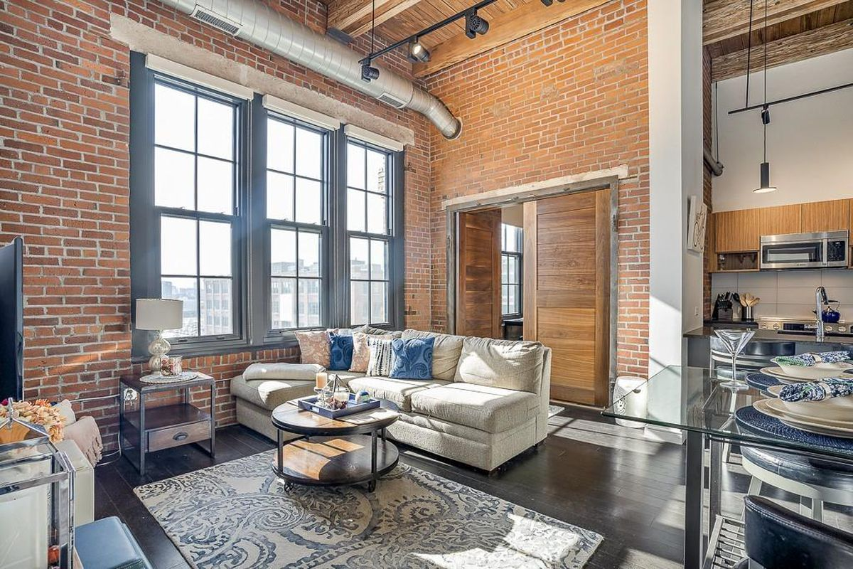 A living room with very high ceilings and very big windows, with furniture and exposed beams and ducts.