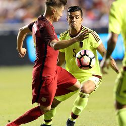 The United States' Jorge Villafana kicks the ball in front of Venezuela's Francisco Flores (5) during a soccer game at Rio Tinto Stadium in Sandy on Saturday, June 3, 2017. They tied 1-1.