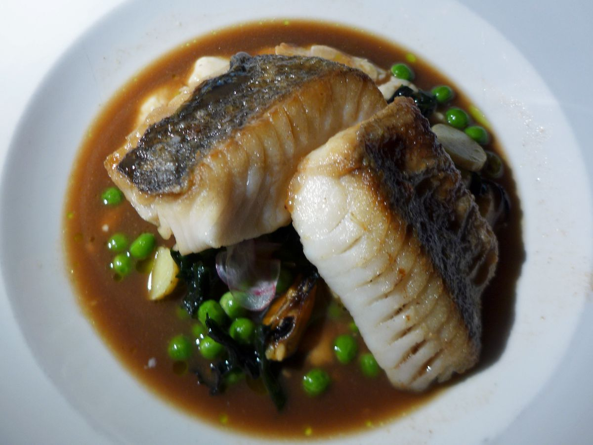Two skin on fish fillets sticking out of a dark broth in a bowl.