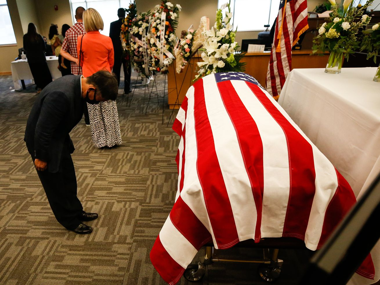 A man bows to the coffin to pay his last respects to Judge Michael Kwan at Taylorsville City Hall in Taylorsville on Friday, July 31, 2020. Kwan died July 21.
