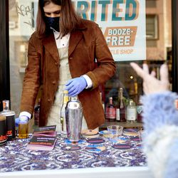 Matthias Laudico, a part-time employee at Spirited Away, speaks with customers participating in a sidewalk tasting in the Lower East Side of Manhattan in New York on Saturday, March 13, 2021. Spirited Away is an alcohol-free bottle shop devoted to everything needed to make alcohol-free cocktails.