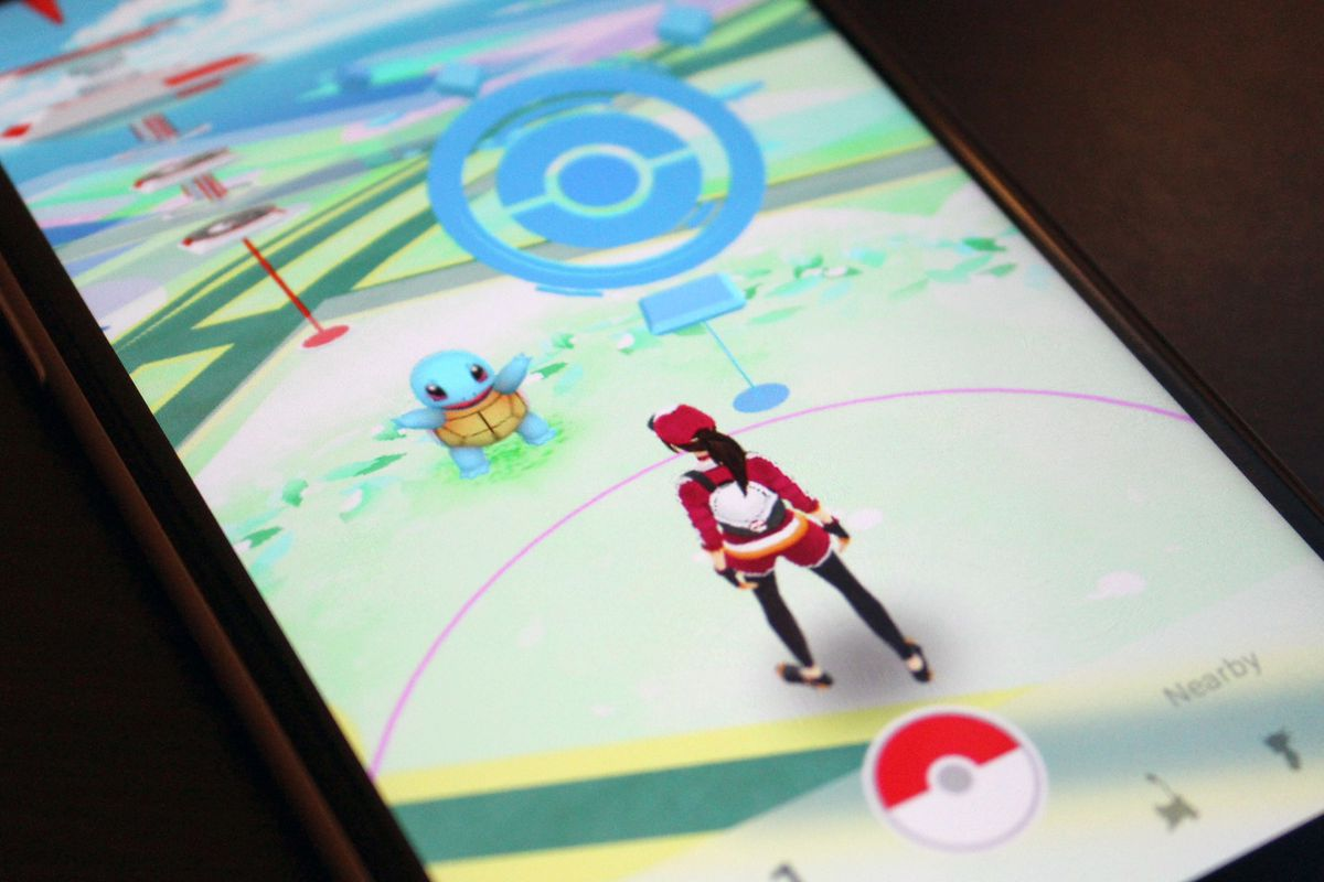 A photo of a phone with a Pokémon Go trainer standing in front of a PokéStop on the screen