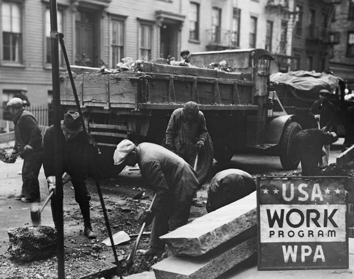 A crew of workers widening a street in the '30s.