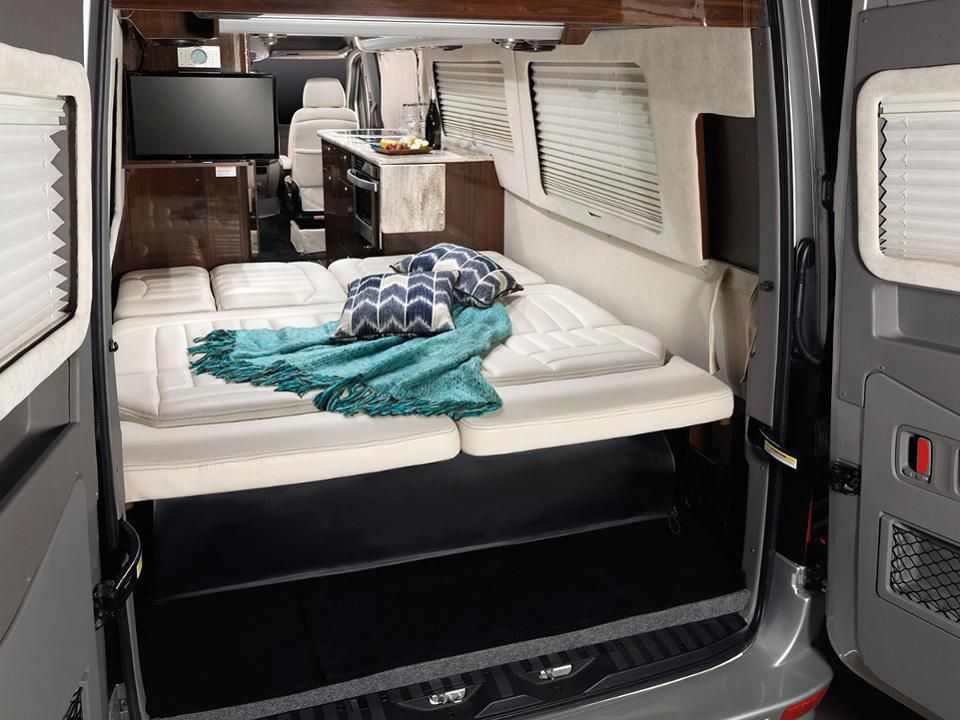 The interior of an RV camper van. The back doors are open revealing a large white bed with a blue blanket and two patterned pillows.