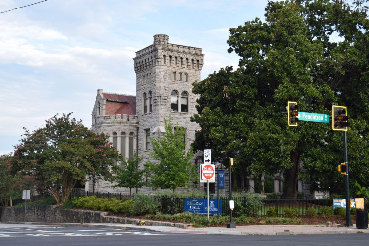 A large magnolia tree by a castle-like building, with street signs and traffic lights in the foreground.