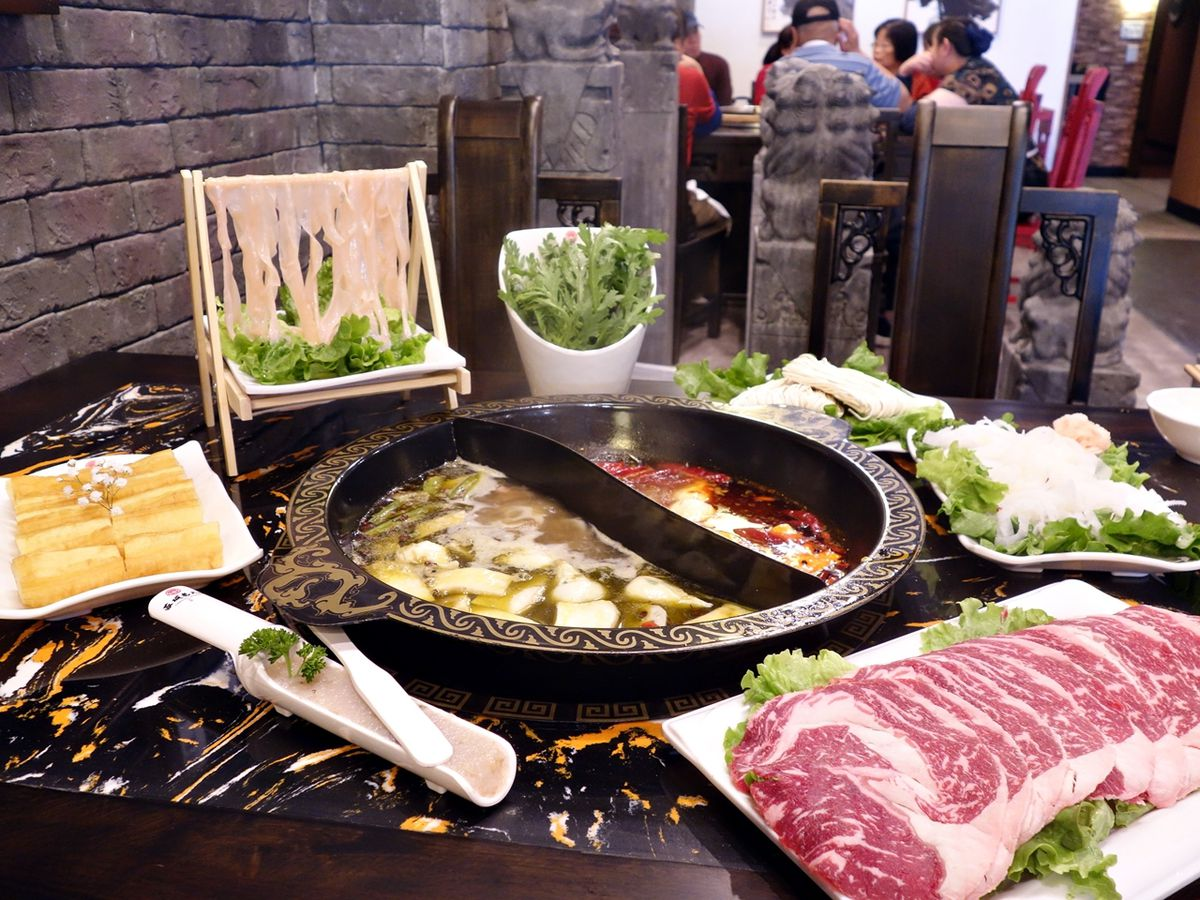 A stone hot pot near a side of raw meat at Chengdu Memory.