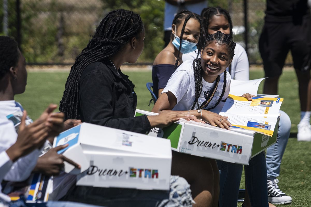 Teasia Sanford smiles with classmates after receiving a Dream Star Capsule on Monday from Dion's Chicago Dream, which presented the capsules to the 2021 8th-grade graduates at Jensen Miller Scholastic Academy at 3030 W. Harrison St. on the West Side.