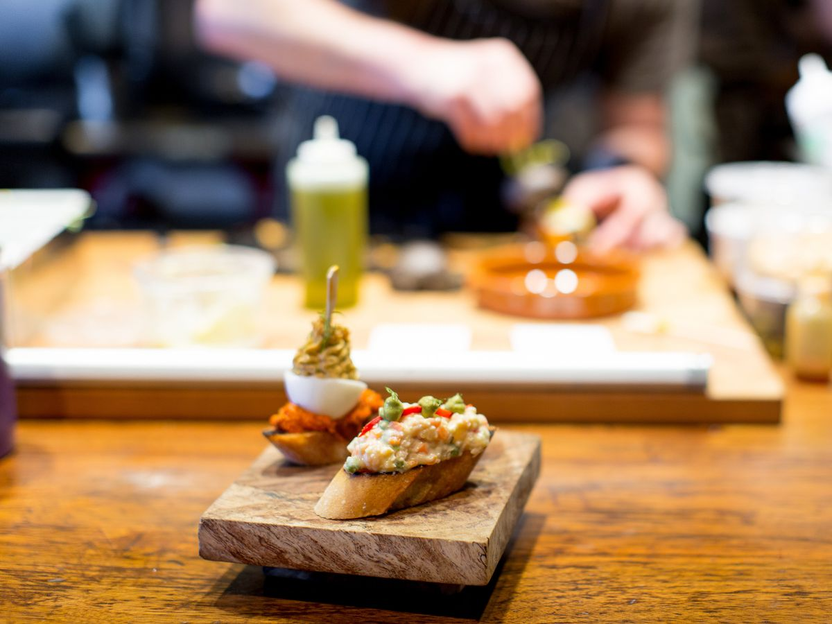 A pintxo sits on a board to be delivered to a table, while chefs continue to prepare dishes in the open-format kitchen