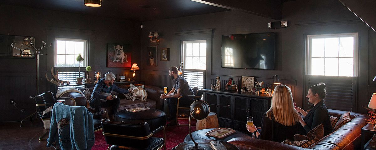 Interior shot of a brewery and distillery's tasting room, which has an intimate living room vibe, featuring leather couches, a bulldog, and smiling people holding drinks