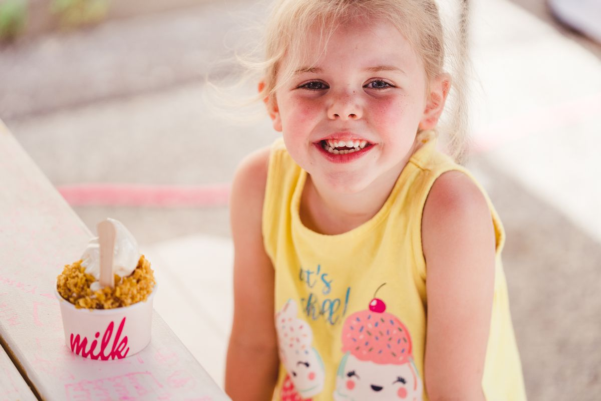 A little girl in an ice cream t-shirt poses with her Cereal Milk soft serve