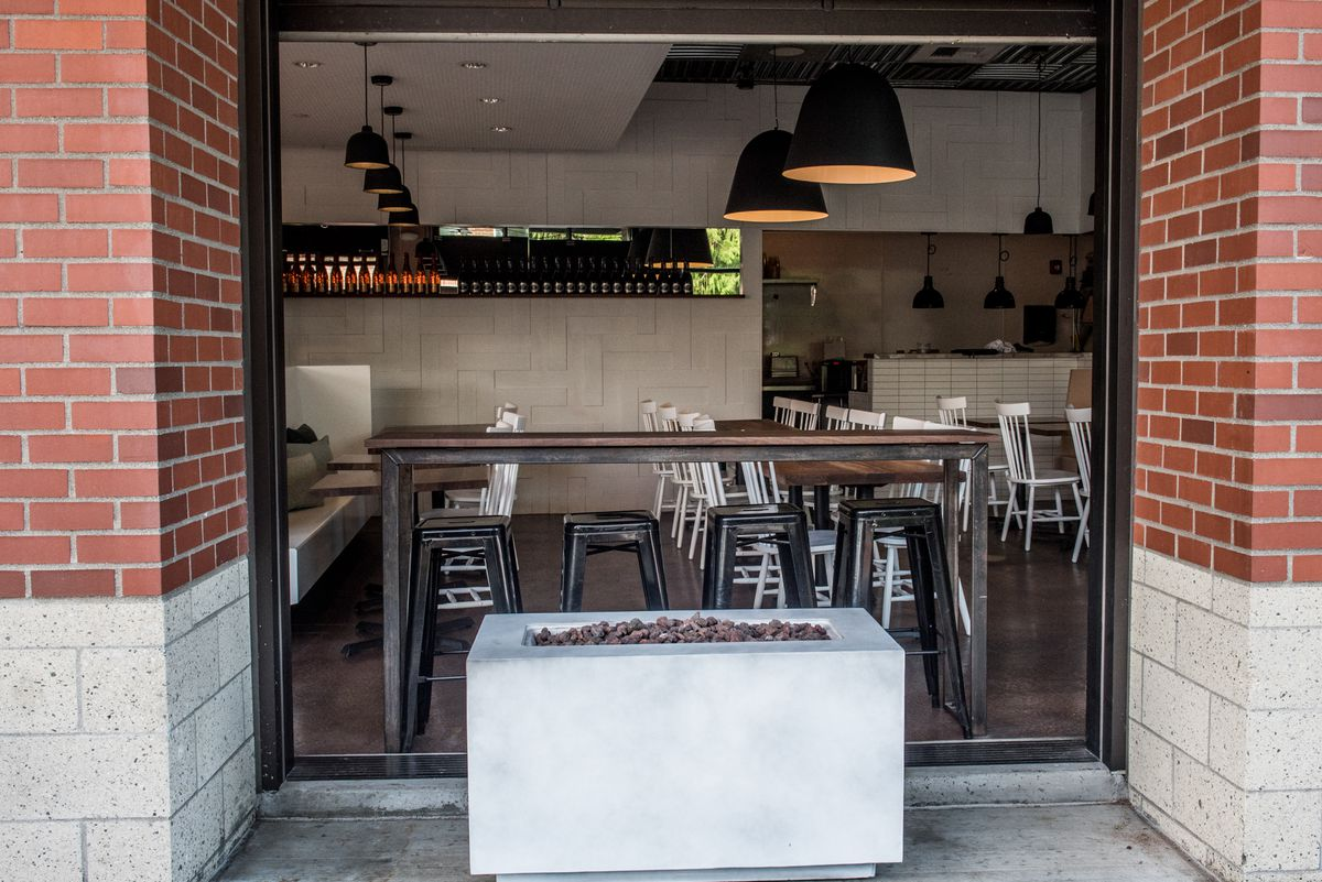 A view from outside Eden Hill Provisions, with a fire pit in the foreground and the dining area in the background.