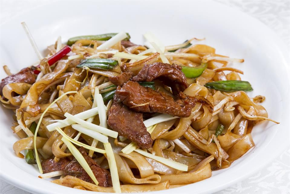 A plate of rice noodles with beef.