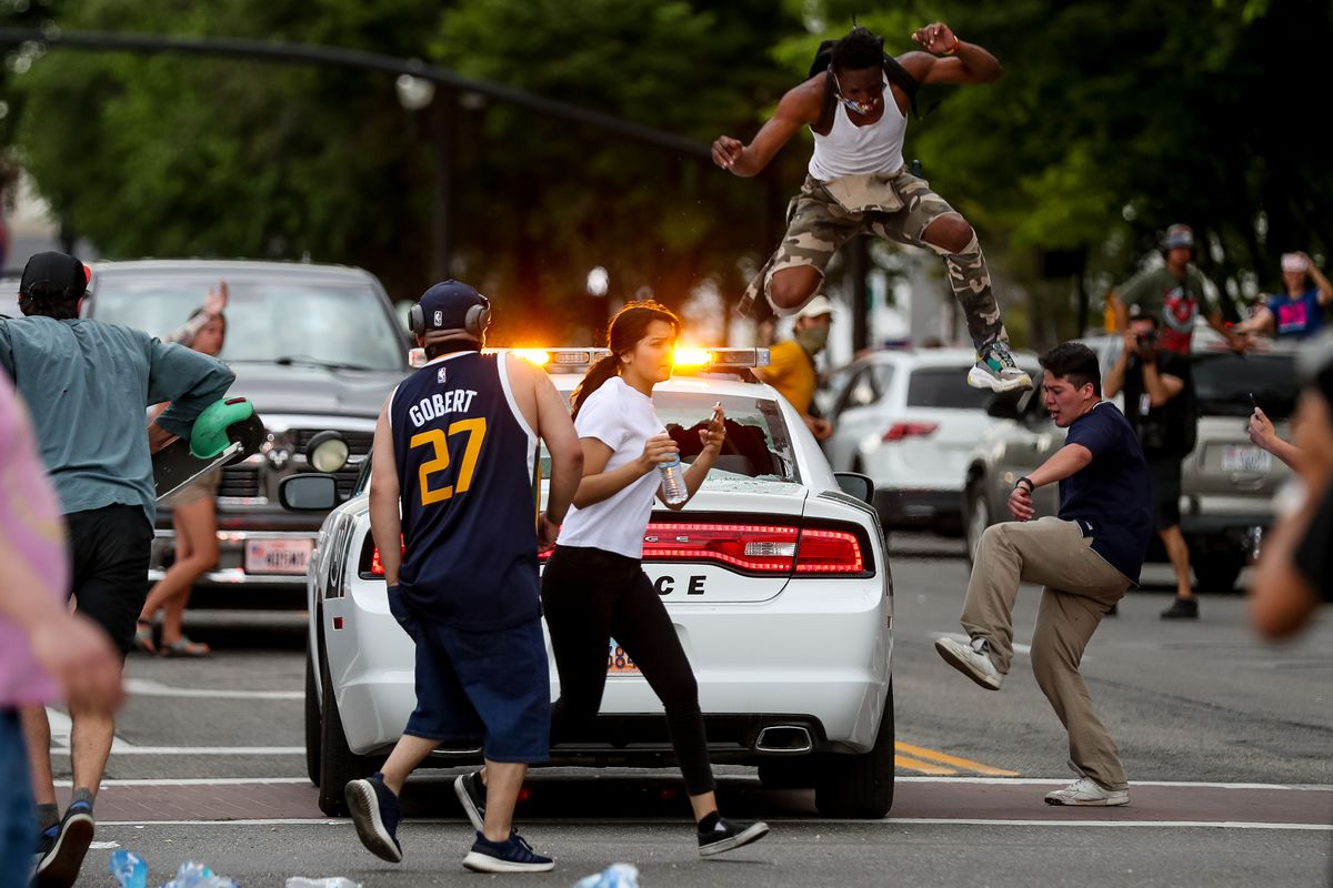 A man leaps out of the way as people smash the windows of a passing police car in downtown Salt Lake City on Saturday, May 30, 2020.Protesters joined others across the nation to decry the death of George Floyd, a black man, who died while being taken into custody by police in Minneapolis earlier this week.