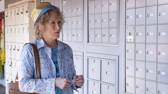 Ellen (Streep), a woman wearing a bucket hat and light blue shirts, stands in front of a row of mailboxes.