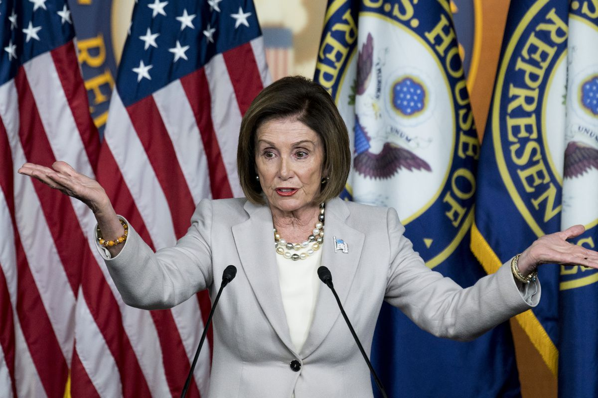 Speaker of the House Nancy Pelosi standing in front of flags and speaking to the press with her arms out and her palms up in a shrugged gesture.