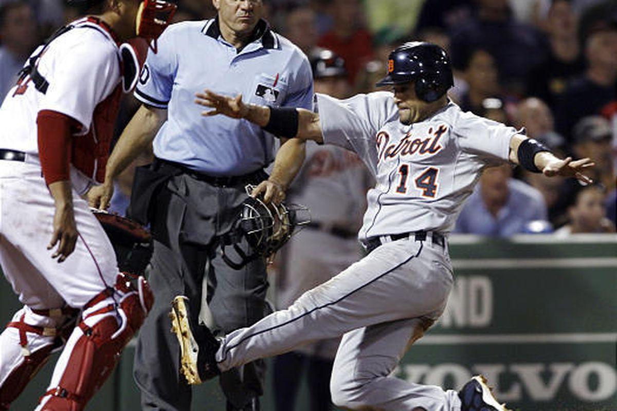 Tiger Placido Polanco, right, scores against Boston Red Sox catcher Victor Martinez.