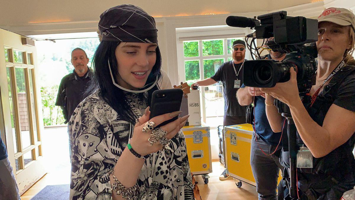 Billie Eilish looks at her phone with sunglasses dangling from her face while a documentary crew points a camera at her