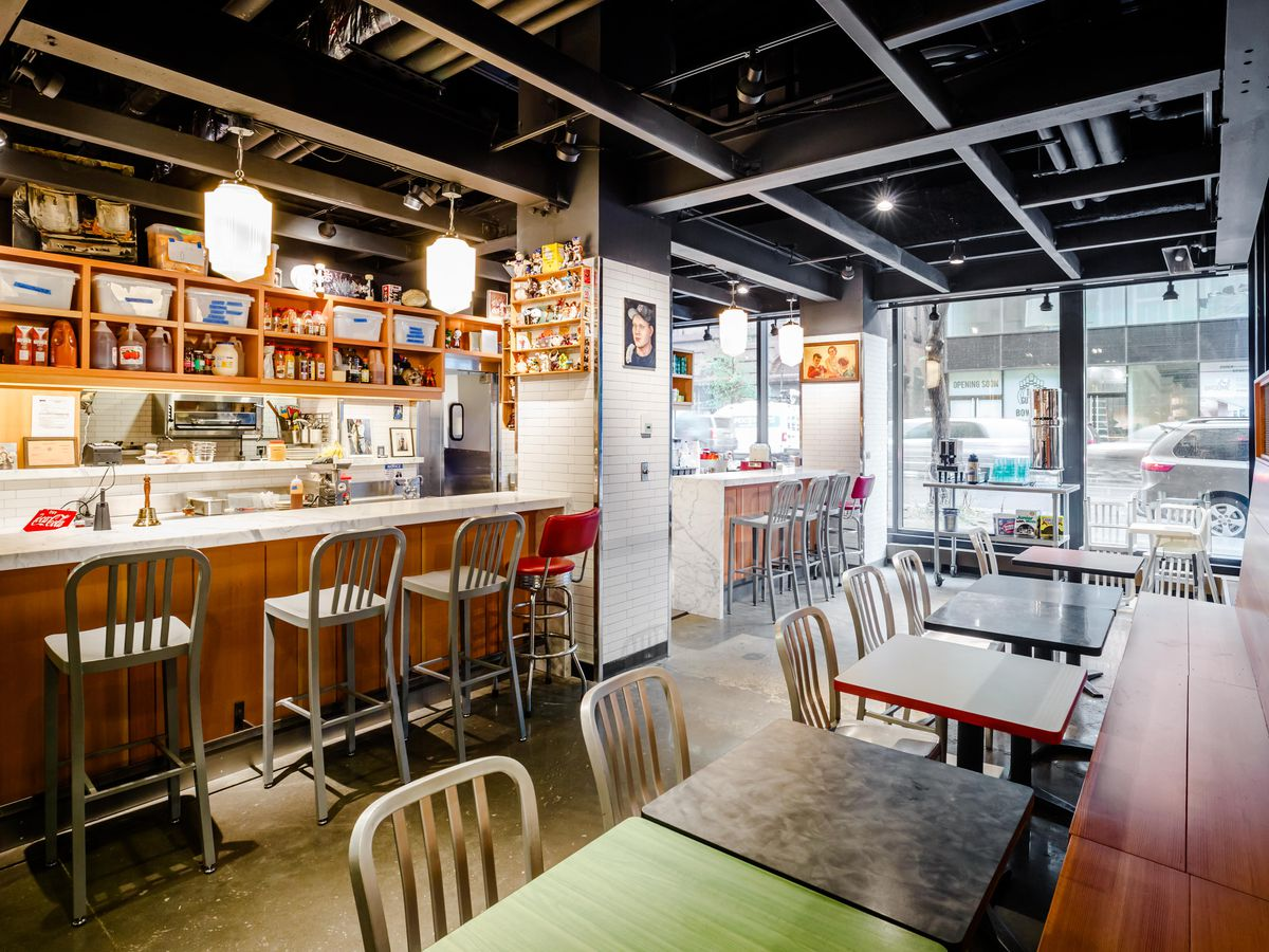 An open kitchen with wooden booths and and high-top counters in the Essex Market