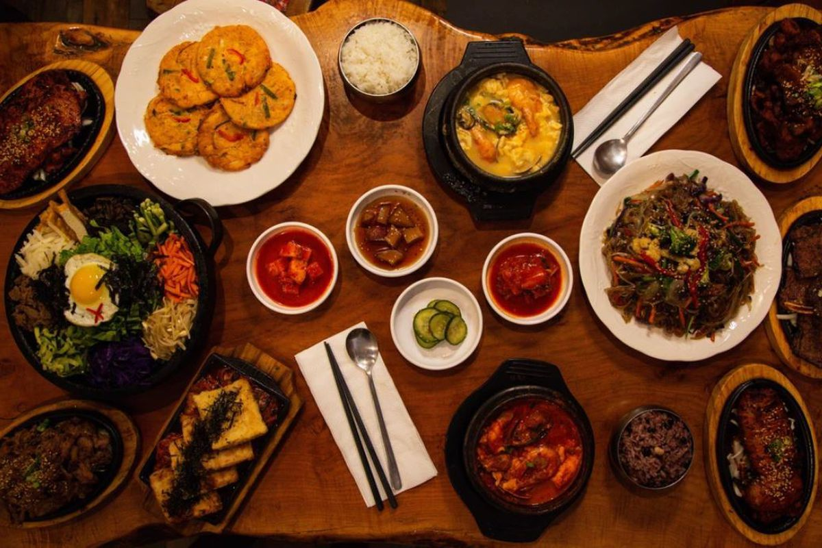 Spread of dishes from Beverly Soon Tofu Korean restaurant in Los Angeles with wood table and metal utensils.