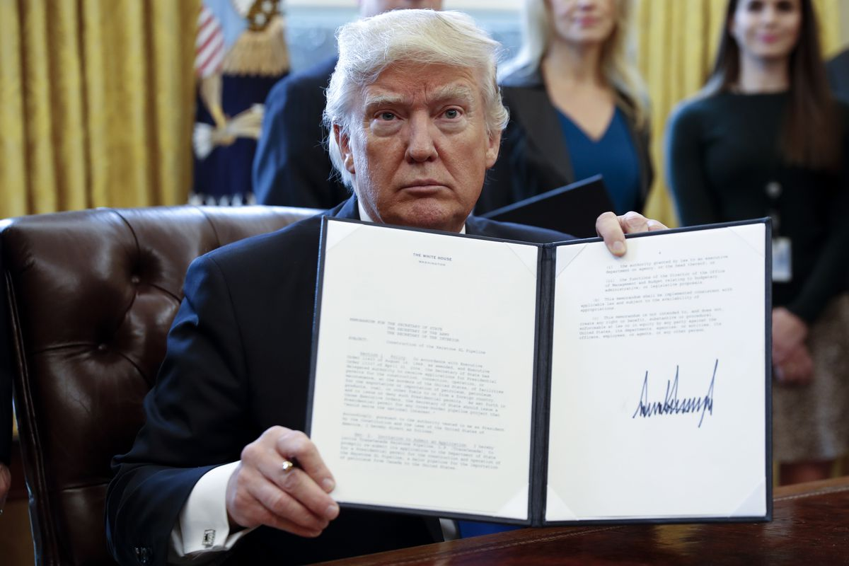 President Donald Trump signs an executive order related to the oil pipeline industry in the Oval Office in January 2017.