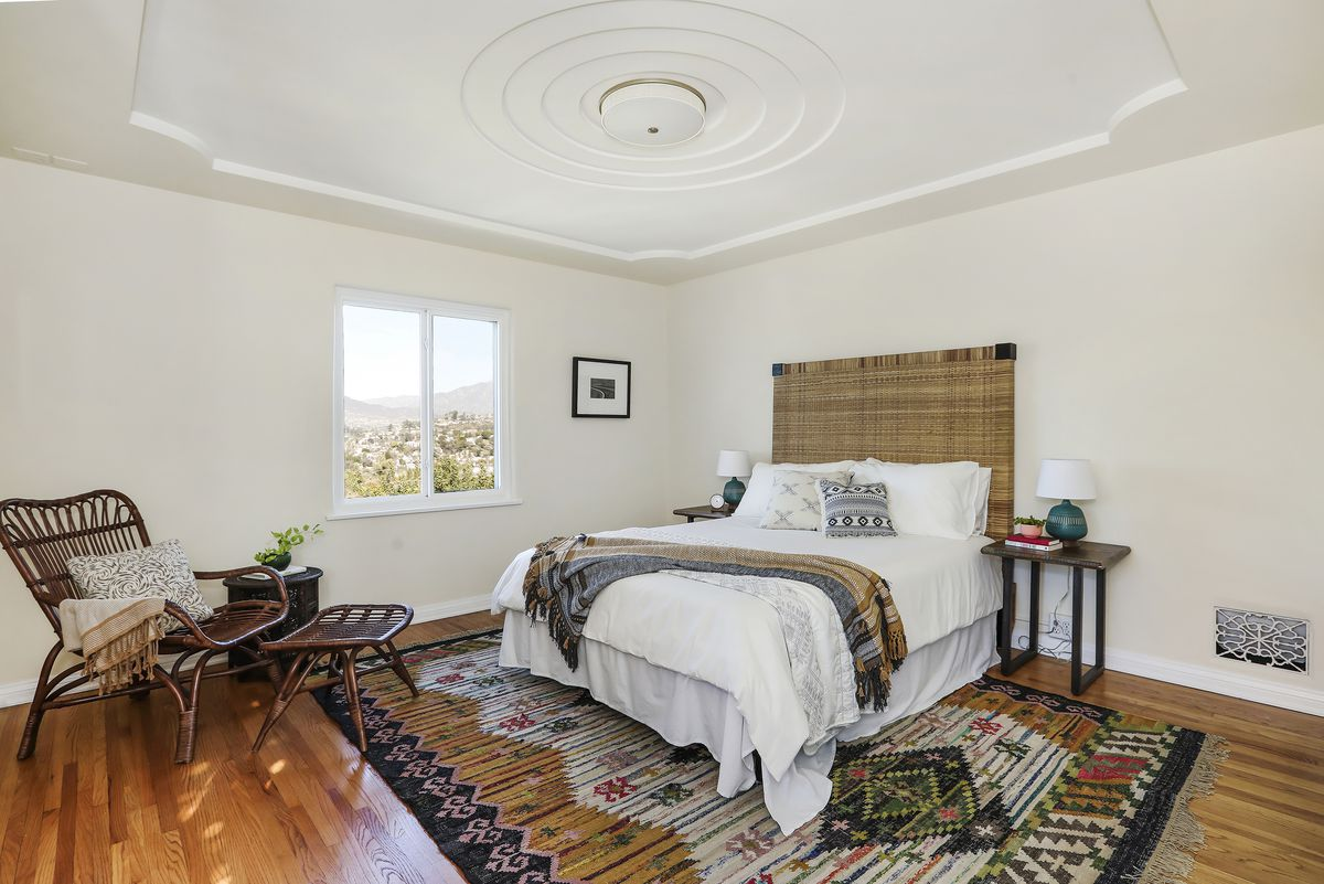 A bedroom with a fancy tray ceiling.