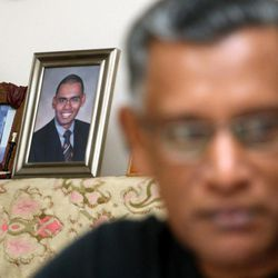 In this photo taken Friday, Sept. 9, 2011, with the backdrop of portraits of the 9/11 terrorist attacks' victim Vijayashanker Paramsothy, his father Paramsothy Sivapakiam, 60, speaks during an interview in Petaling Jaya, near Kuala Lumpur, Malaysia. Sivapakiam said he had to learn to deal with burning hatred and anger against the terrorists who took his son's life.