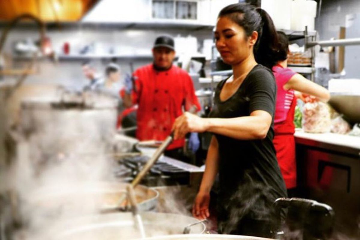A woman stands beside a bubbling cauldron of soup inside Quang's kitchen