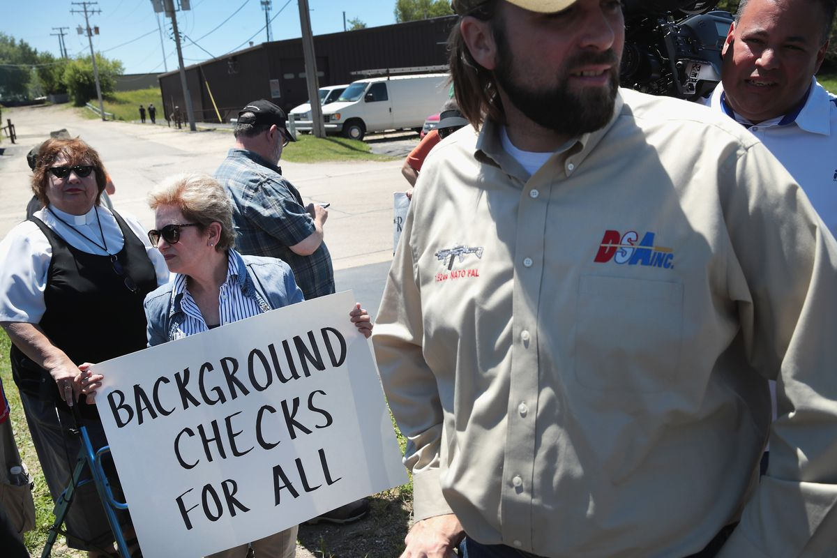 """Woman holding """"background checks for all"""" sign"""