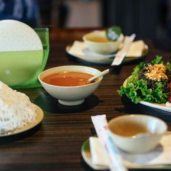An assortment of accoutrements, including herbs, rice noodles, and rice paper with warm water for dipping hit the table as you await your whole baked fish.