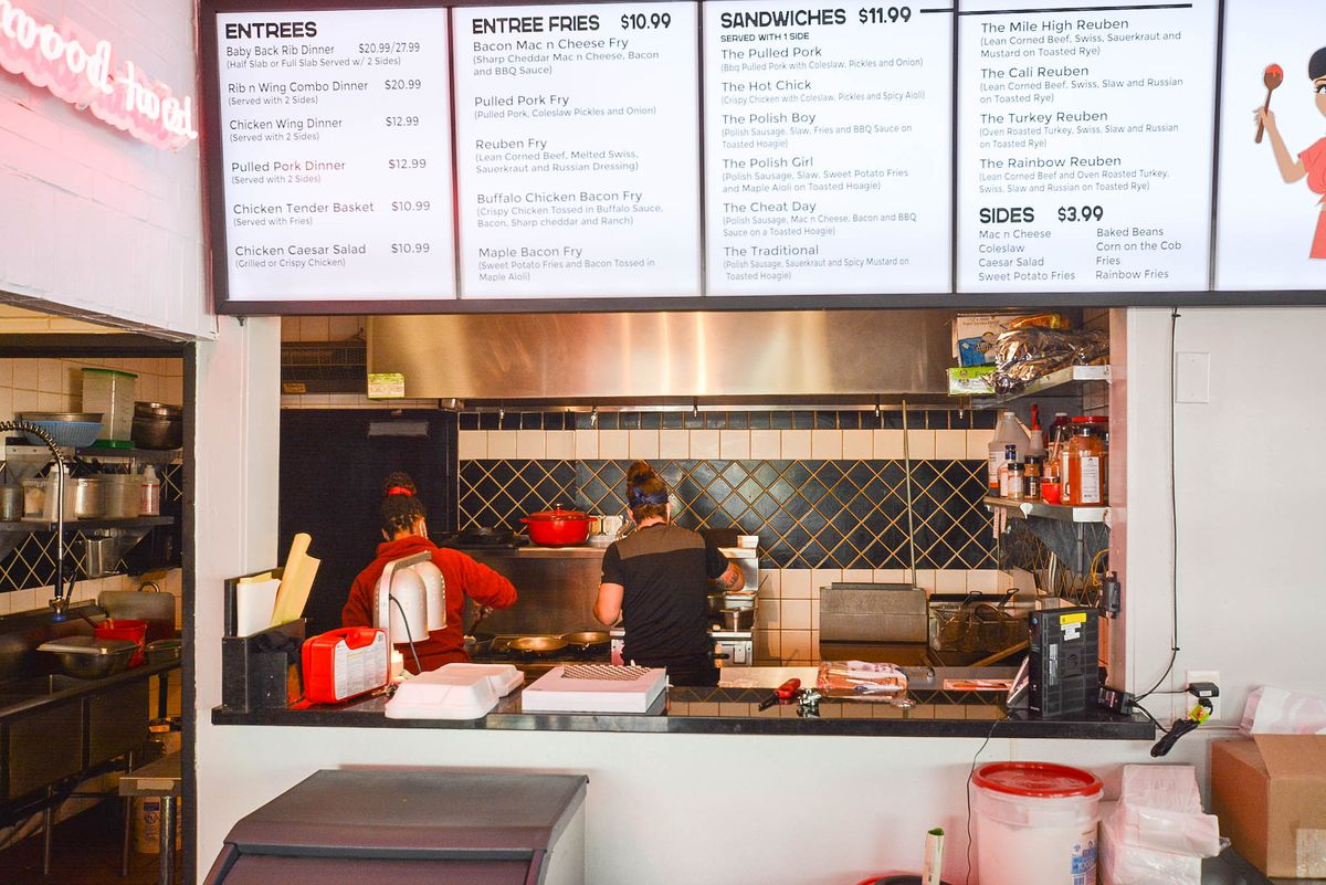 Two people with their backs turned inside of a new open restaurant kitchen.