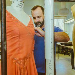 Costume shop manager Jason Hadley fixes the straps of a Carolina Herrera costume.