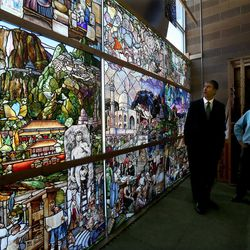 """Utah Valley University President Matthew Holland, left, and Tom and Gayle Holdman look at the progress of """"Roots of Knowledge"""" at Holdman Studios at Thanksgiving Point in Lehi on Friday, Sept. 16, 2016. A Guardian UK reporter called the work """"one of the most spectacular stained glass windows made in the past century."""""""