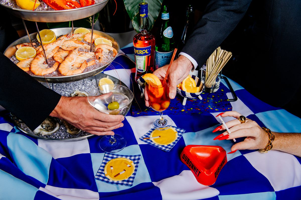 Two suited arms reach past a seafood tower to lift cocktails from fabric coasters as a hand with long red nails holds a cigarette aloft