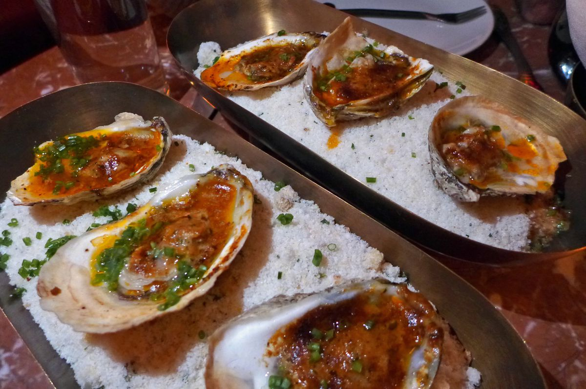 Six oysters on a bed of salt, each with a pool of red fluid hot from the oven.