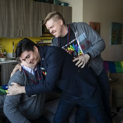 Matt Schreck (right), 43, his husband, Fernando Gutierrez, 41, and their friend Brian Dowling, 39, cheer and hug during the inauguration ceremony for President Joe Biden and Vice President Kamala Harris at Schreck and Gutierrez's South Loop home, Wednesday morning, Jan. 20, 2021.