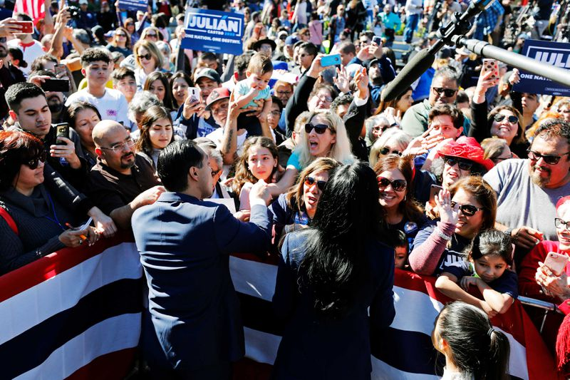 A large crowd surrounds Julián Castro and his wife Erica Lira Castro.