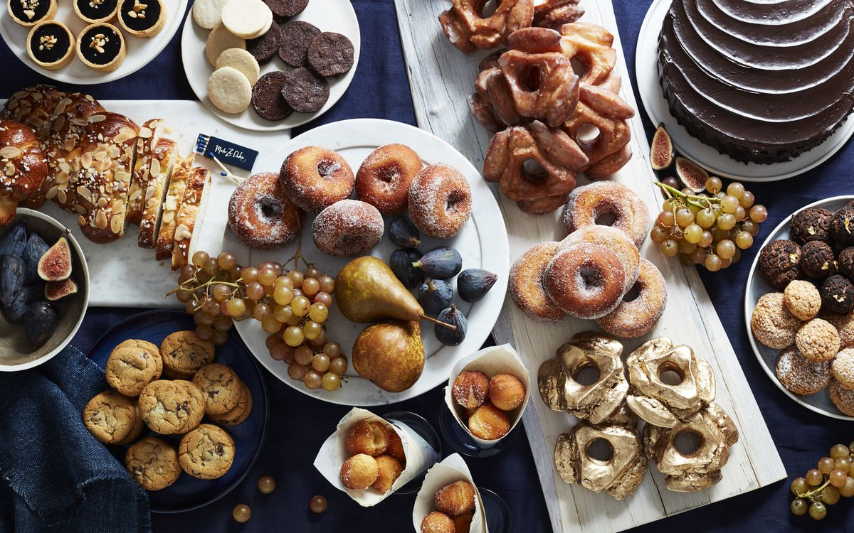 A crowded array of pastries, cookies, cakes, and fruit on plates and platters over a dark blue tablecloth.