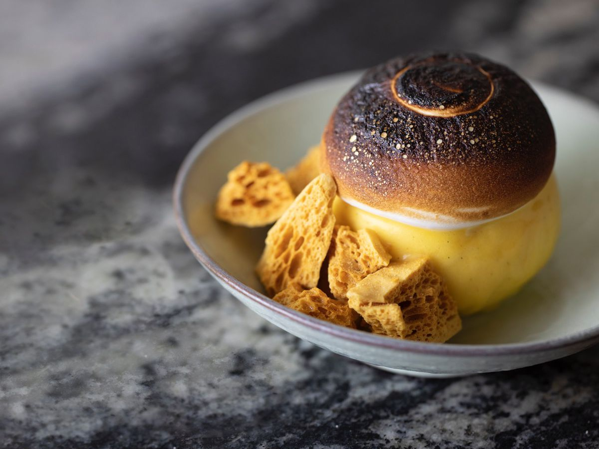 A sundae with a burnt, crispy top sits in a shallow bowl with bits of honeycomb candy served on the side.