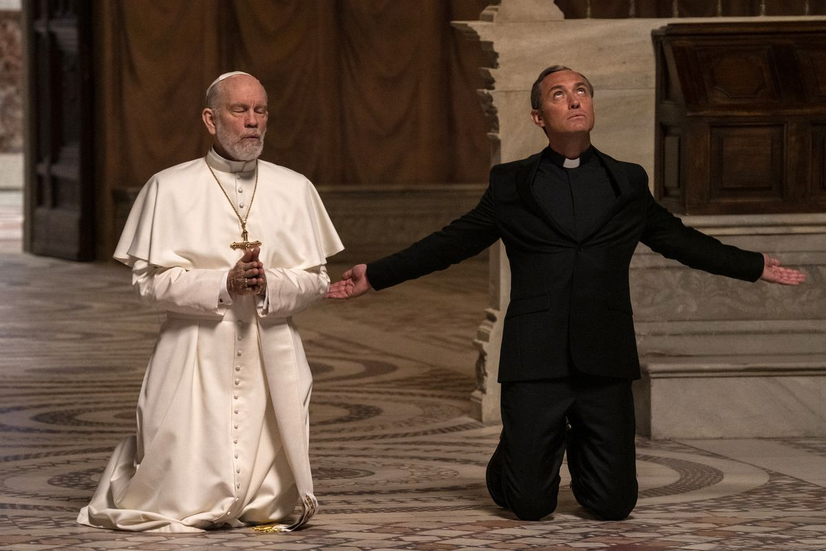 John Malkovich, wearing white papal robes and skullcap, and a gold crucifix, kneels in prayer with his eyes closed and hands folded together. Next to him, Jude Law, in a black suit and priest's collar, kneels with his arms spread wide and looks up to heaven.