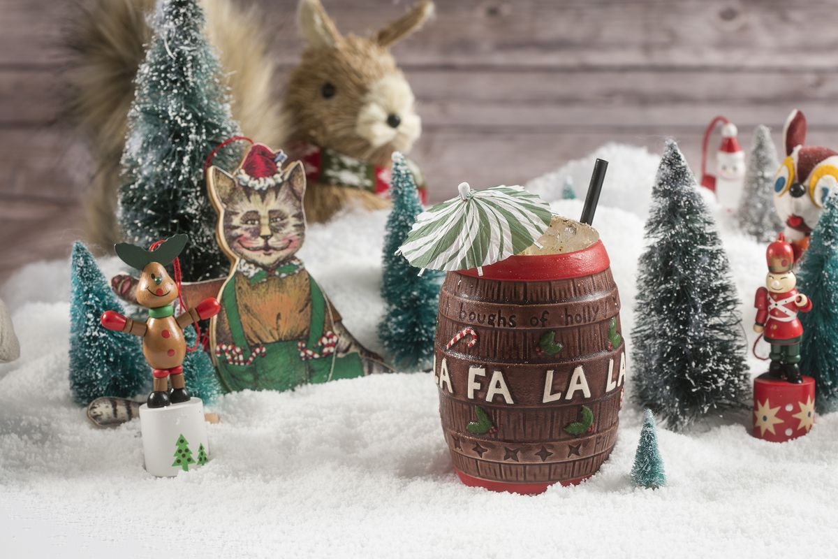 """A tiki drink is served in a Christmas-themed cup shaped like a barrel with """"fa la la"""" written on it. The drink is set on a Christmas backdrop with fake snow, trees, and other festive knick-knacks."""