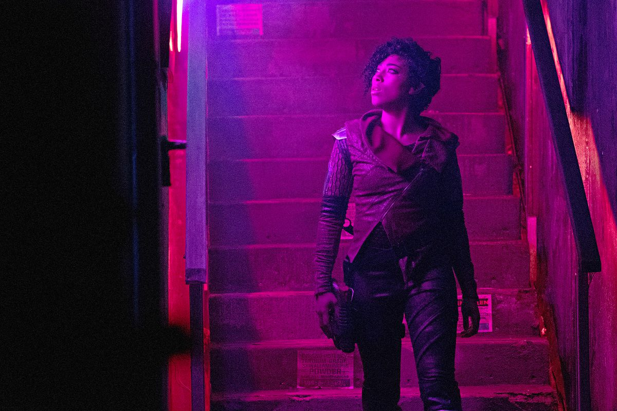 Adriyan Rae as Queen Elida stands at the bottom of some stairs and looks upward in a neon-lit red-purple space.