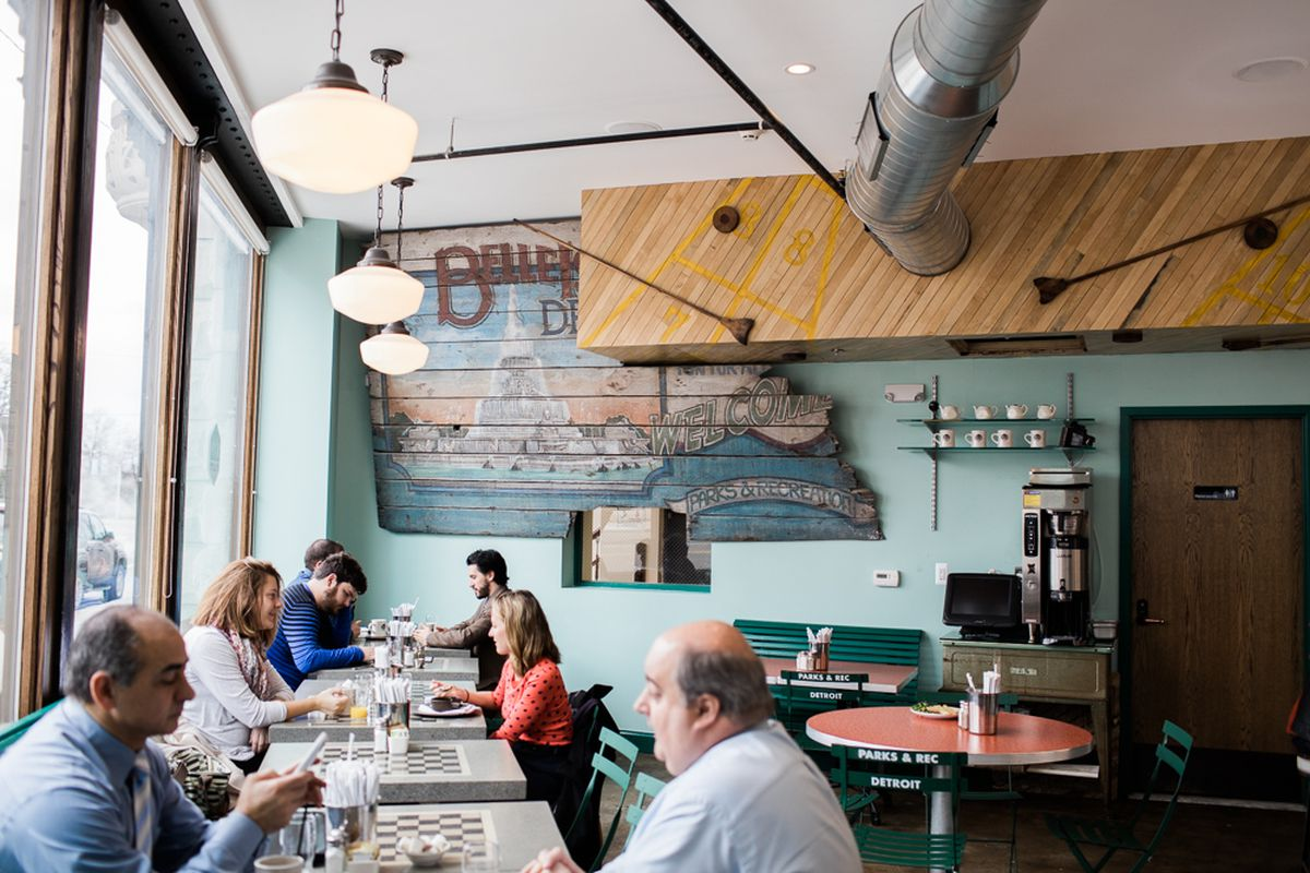 People eat at two-top laminate tables near the windows inside Parks & Rec diner.