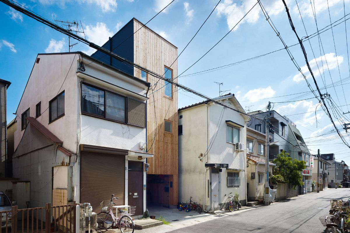 Narrow timber-clad house squeezes between two, more traditional homes on a residential street in Japan.