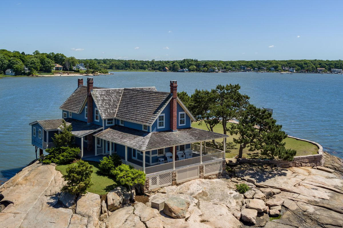 An exterior view of a cottage on a rocky island with water all around it.