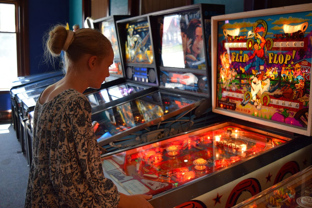 Photo of a young woman playing a vintage pinball machine