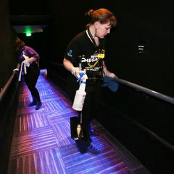 McKenzie Horrocks, left, and Nicki Forbes clean handrails after cleaning the seats and food trays between movies at the Megaplex Theatres at Jordan Commons in Sandy on Friday, March 13, 2020.