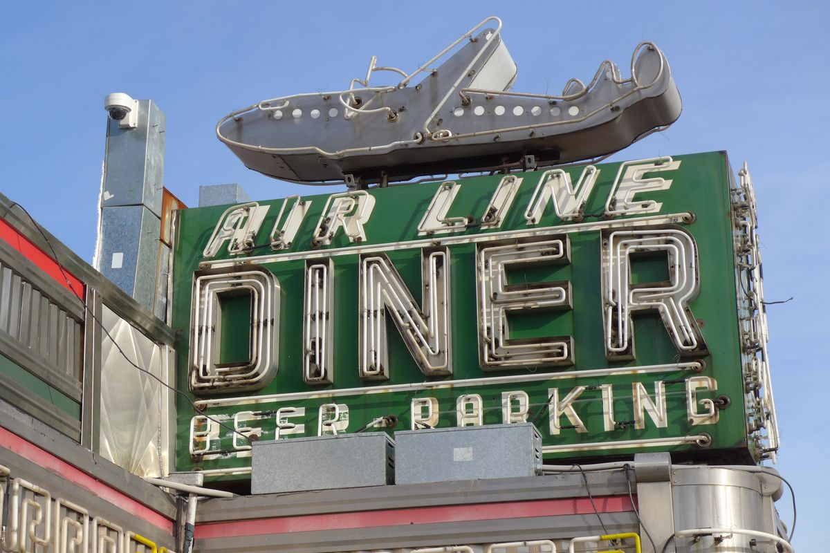 A metal sign with lots of unlit neon says Air Line Diner with an old fashioned passenger airplane on top.
