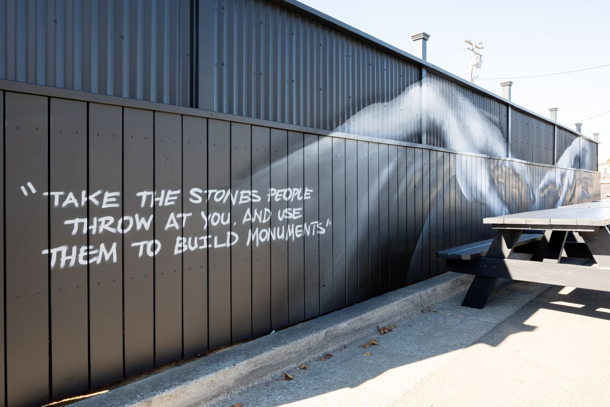 """A mural outside the restaurant reads """"Take the stones people throw at you and use them to build monuments."""""""