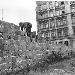 An East Berlin policeman puts bricks in place as the Berlin Wall is heightened to 15 feet, 5 m, separating East and West Berlin, Germany, on Sept. 9, 1961.  People watch from their apartment building windows in background above.